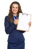 Smiling business woman pointing in blank clipboard Royalty Free Stock Photo