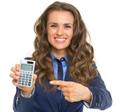 Smiling business woman pointing on calculator Royalty Free Stock Images