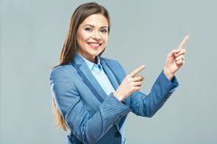 Smiling business woman  pointing finger on copy space. Business style suit. Young model with long hair Royalty Free Stock Images