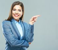 Smiling business woman  pointing finger on copy space. Business style suit. Young model with long hair Royalty Free Stock Image