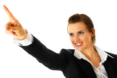 Smiling business woman pointing finger in corner Stock Images