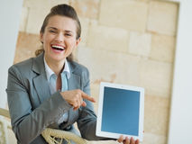 Smiling business woman pointing on tablet PC Stock Image
