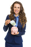 Smiling business woman putting 100 euro banknote into piggy bank. Isolated on white Royalty Free Stock Images