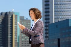 Smiling business woman reading text message on cell phone Royalty Free Stock Photo
