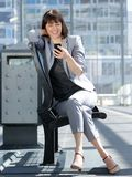 Smiling business woman reading text message on mobile phone Stock Photography