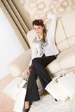 Smiling business woman with shopping bag on sofa Stock Photo