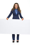 Smiling business woman showing blank billboard Stock Image