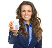 Smiling business woman showing calculator Royalty Free Stock Images
