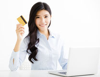 Smiling business woman showing credit card in office Stock Photos