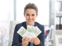 Smiling business woman showing money packs Stock Image