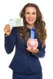 Smiling business woman showing one hundred euros and piggy bank royalty free stock image