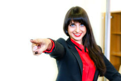 Smiling business-woman shows finger forward. Focus on finger Royalty Free Stock Photos