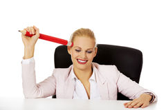 Smiling business woman sitting behind the desk and holding huge pen Stock Photos