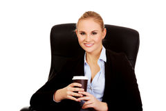 Smiling business woman sitting on a chair and holding cup of coffee Stock Photo