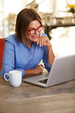 Smiling business woman sitting at desk working on laptop Royalty Free Stock Photography