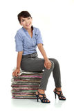 Smiling business woman sitting on documents Stock Photo