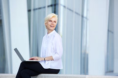 Smiling business woman sitting outside with laptop. Stock Photography