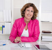 Smiling business woman sitting satisfied at desk. Stock Photo