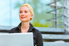 Smiling business woman sitting on stairs at office. Smiling modern business woman sitting on stairs at office building and using laptop Royalty Free Stock Photo