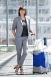 Smiling business woman standing at airport with bag Royalty Free Stock Images