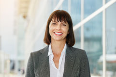Smiling business woman standing in the city Stock Photo