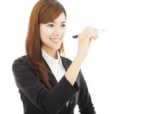 Smiling business woman standing and holding a pencil Stock Photo