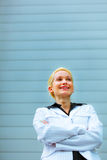 Smiling business woman standing near office stock images