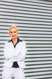 Smiling business woman standing at office building stock image