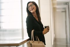 Female executive standing in office during break. Smiling business woman standing in office with cup of coffee . Female executive standing in office during break Royalty Free Stock Photo