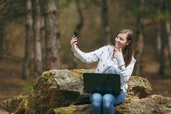 Smiling business woman or student sitting on stone with laptop doing selfie and pointing finger on mobile phone in city royalty free stock images