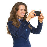 Smiling business woman taking photo using cell phone Stock Images