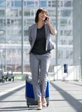 Smiling business woman talking on mobile phone at airport Royalty Free Stock Photo