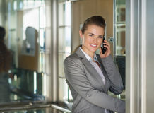 Smiling business woman talking phone in elevator Stock Images
