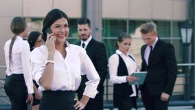 Smiling business woman talking on the phone and her colleagues in the background and chatting positively stock video