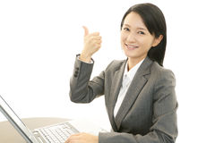 Smiling business woman with thumbs up. Asian business woman sitting at desk working on laptop Royalty Free Stock Photo