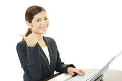 Smiling business woman with thumbs up. Asian business woman sitting at desk working on laptop Royalty Free Stock Photography