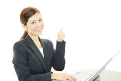 Smiling business woman with thumbs up. Asian business woman sitting at desk working on laptop Stock Photo