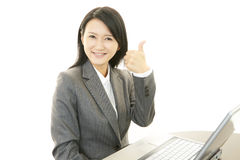 Smiling business woman with thumbs up. Asian business woman sitting at desk working on laptop Royalty Free Stock Image