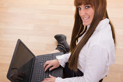 Smiling business woman typing on laptop keyboard on the floor. Smiling business woman typing on laptop keyboard sitting on the floor Stock Images