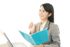 Smiling business woman using laptop. Asian business woman sitting at desk working on laptop Royalty Free Stock Photography