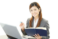 Smiling business woman using laptop. Asian business woman sitting at desk working on laptop Stock Image