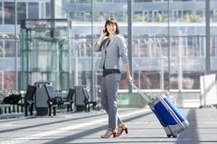 Smiling business woman walking with bag and mobile phone Royalty Free Stock Photography