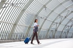 Smiling business woman walking with bag at station Royalty Free Stock Images