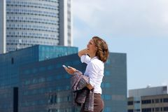 Smiling business woman walking in the city with cell phone Stock Photo