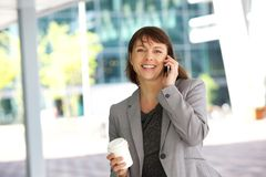 Smiling business woman walking and talking on cell phone Stock Photo