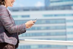 Smiling business woman walking and using mobile phone Royalty Free Stock Photo