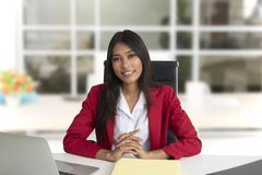 Smiling business woman wearing red suit sitting in office royalty free stock images