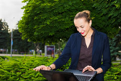 Smiling business woman. Working on her laptop outdoors Royalty Free Stock Photography