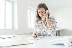 Smiling business woman working at her office desk making a phone Stock Images