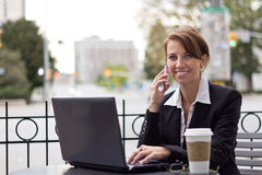 Smiling business woman working on telephone at outdoor coffee sh Stock Images